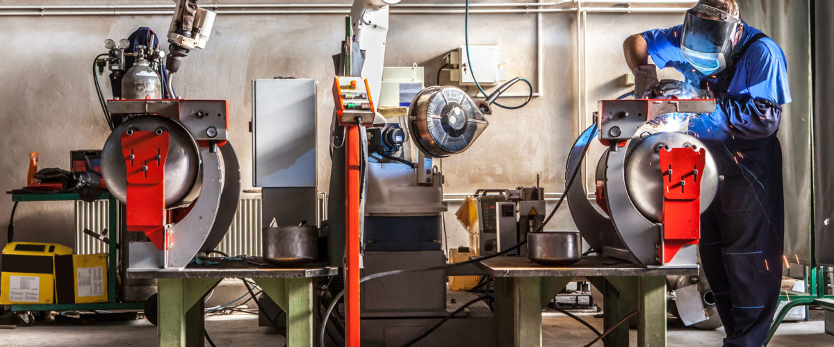The mechanical performs welds metal components assisted by a worker.